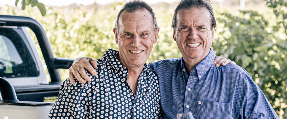Mal and Bruce standing behind their Ute with their arms around each other